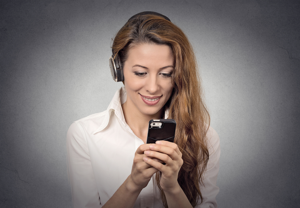 Closeup portrait happy looking, surprised businesswoman with headphones reading news, sms on smart phone holding mobile listening radio podcast isolated grey background. Human face expression, emotion
